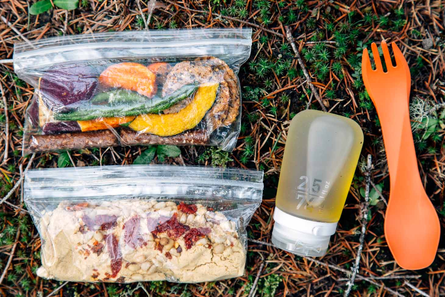 Ingredients for backpacking hummus in ziplock bags on a forest floor.