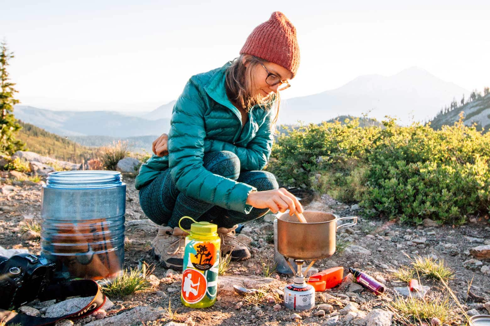 Woman cooking a meal on a backpacking stove.