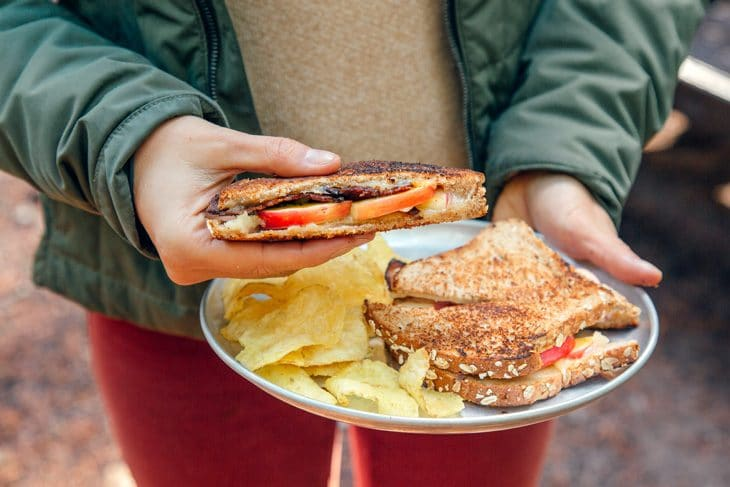 Megan holding a plate with grilled cheese and chips. She is holding one of the sandwiches.