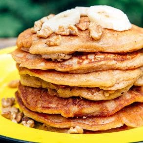 A stack of pancakes topped with sliced bananas on a yellow plate.