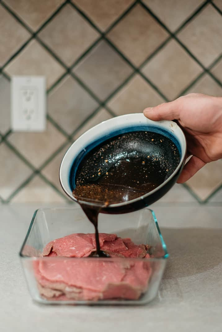 Pouring marinade for beef jerky into a bowl