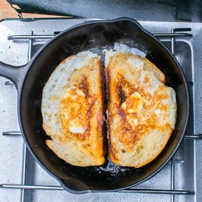 Two pieces of toast with eggs in the center in a skillet