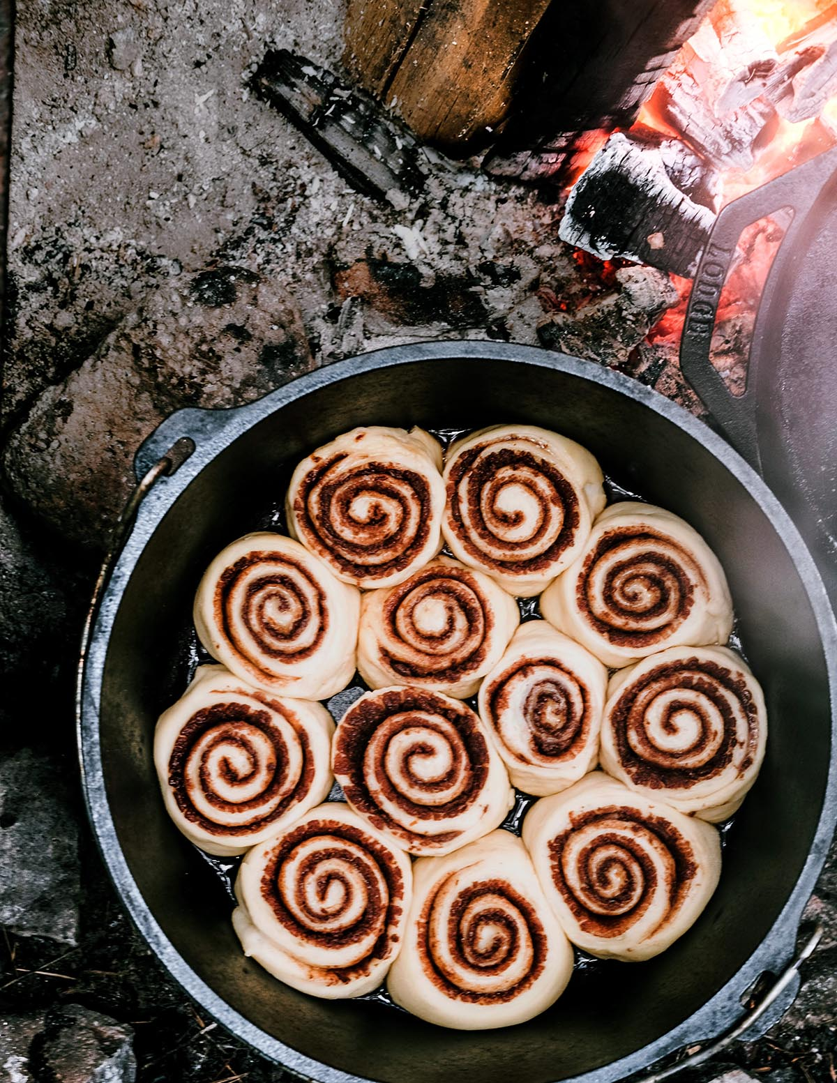 Cinnamon rolls in a Dutch oven next to a campfire