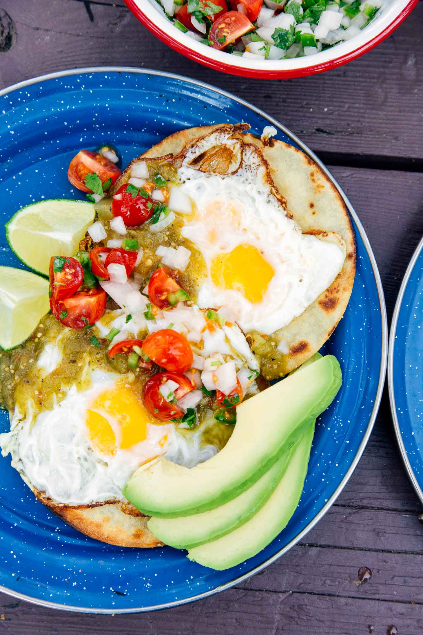 Two tortillas topped with eggs, salsa, and sliced avocado