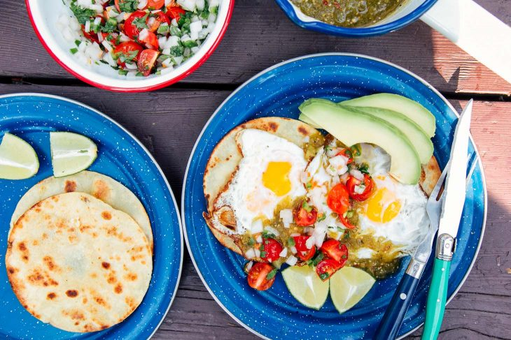 Eggs, salsa, and avocado on top of tortillas on blue camping plates.