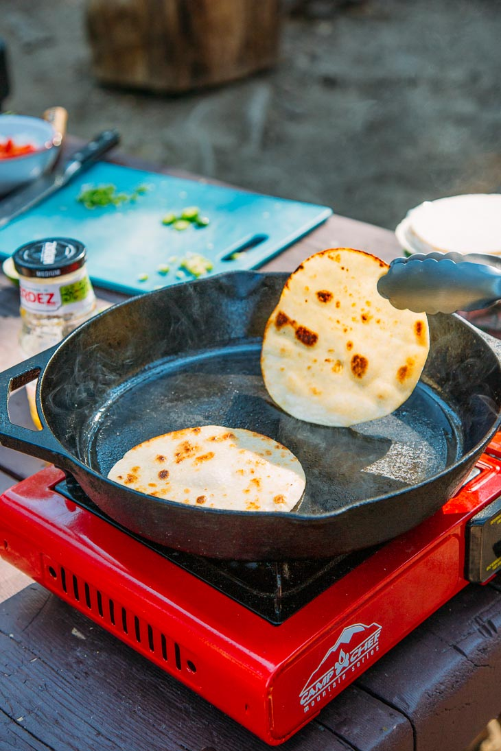 Tongs flipping a tortilla in a skillet