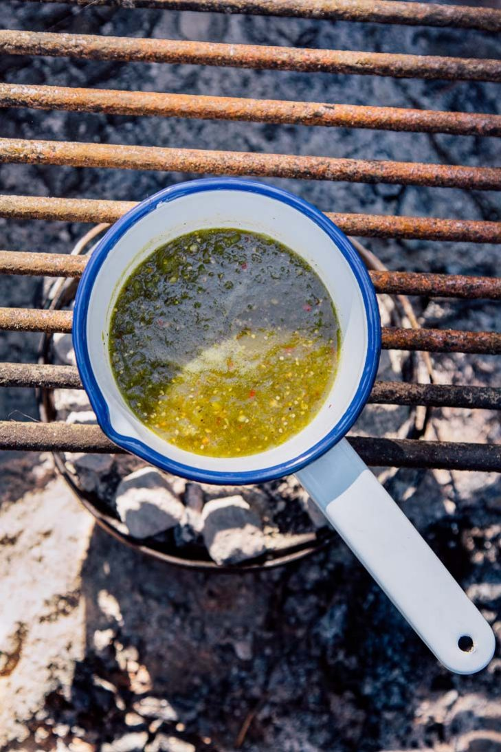 A small pot of salsa verde over a campfire
