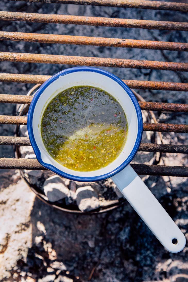 A small pot of salsa verde over a campfire