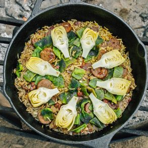Rice, sausage, artichoke hearts, and poblano pepper arranged in a skillet over a campfire