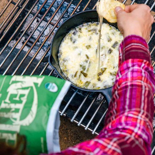 Dipping a chip into a skillet of queso fundido on a campfire.