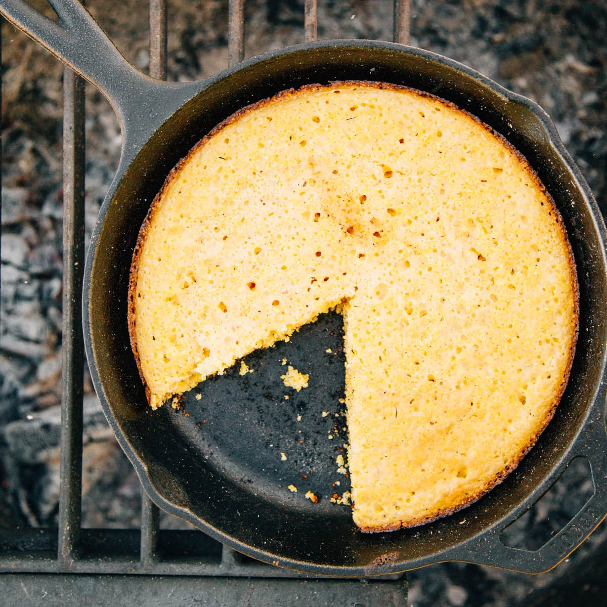 Cornbread with a slice taken out in a cast iron skillet