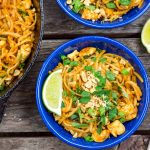 Two bowls of Pad thai and a wedge of lime next to a skillet on a wooden surface