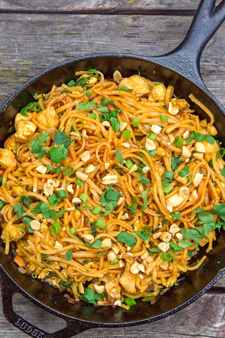 Chicken pad thai in a skillet on a wooden surface