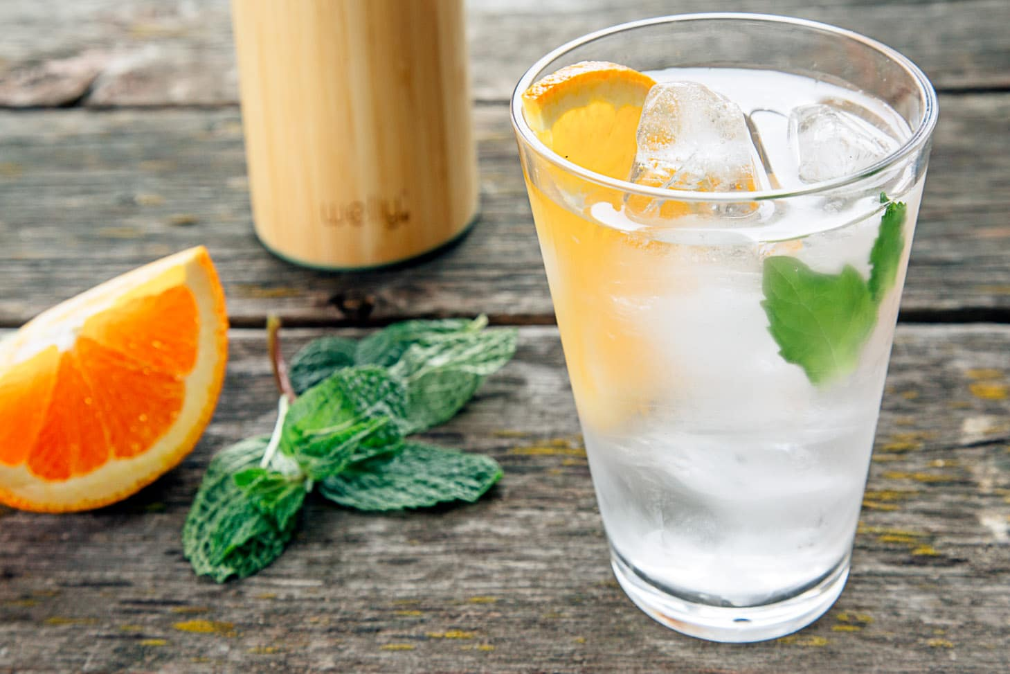 Infused water with oranges and mint in a tall glass.