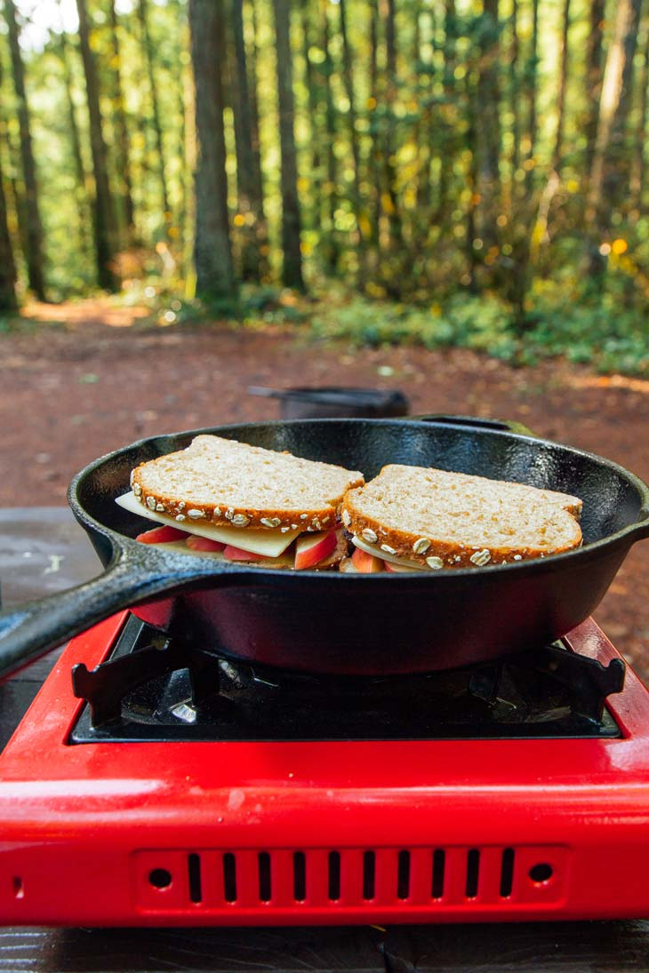 Grilled cheese sandwiches in a skillet on a camp stove with forest in the background