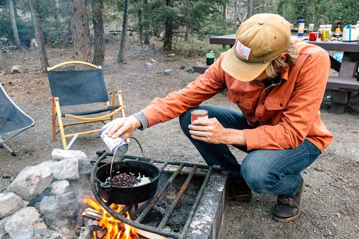 Man cooking over a campfire with a Dutch oven