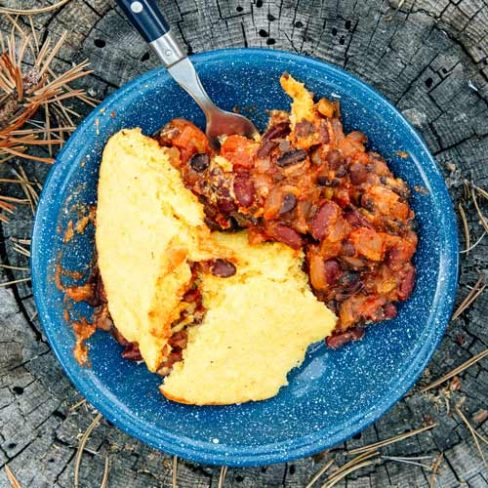 A bowl of chili and cornbread on a tree stump