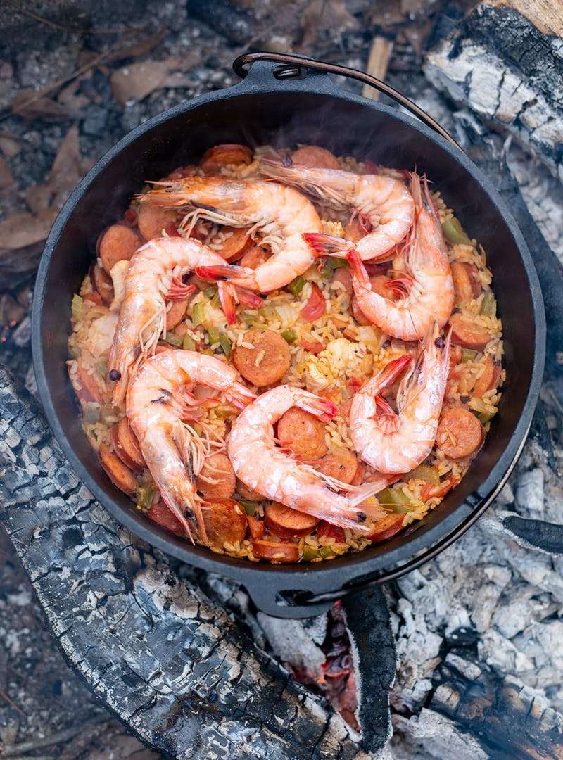 Jambalaya topped with seven large shrimp in a Dutch oven over coals