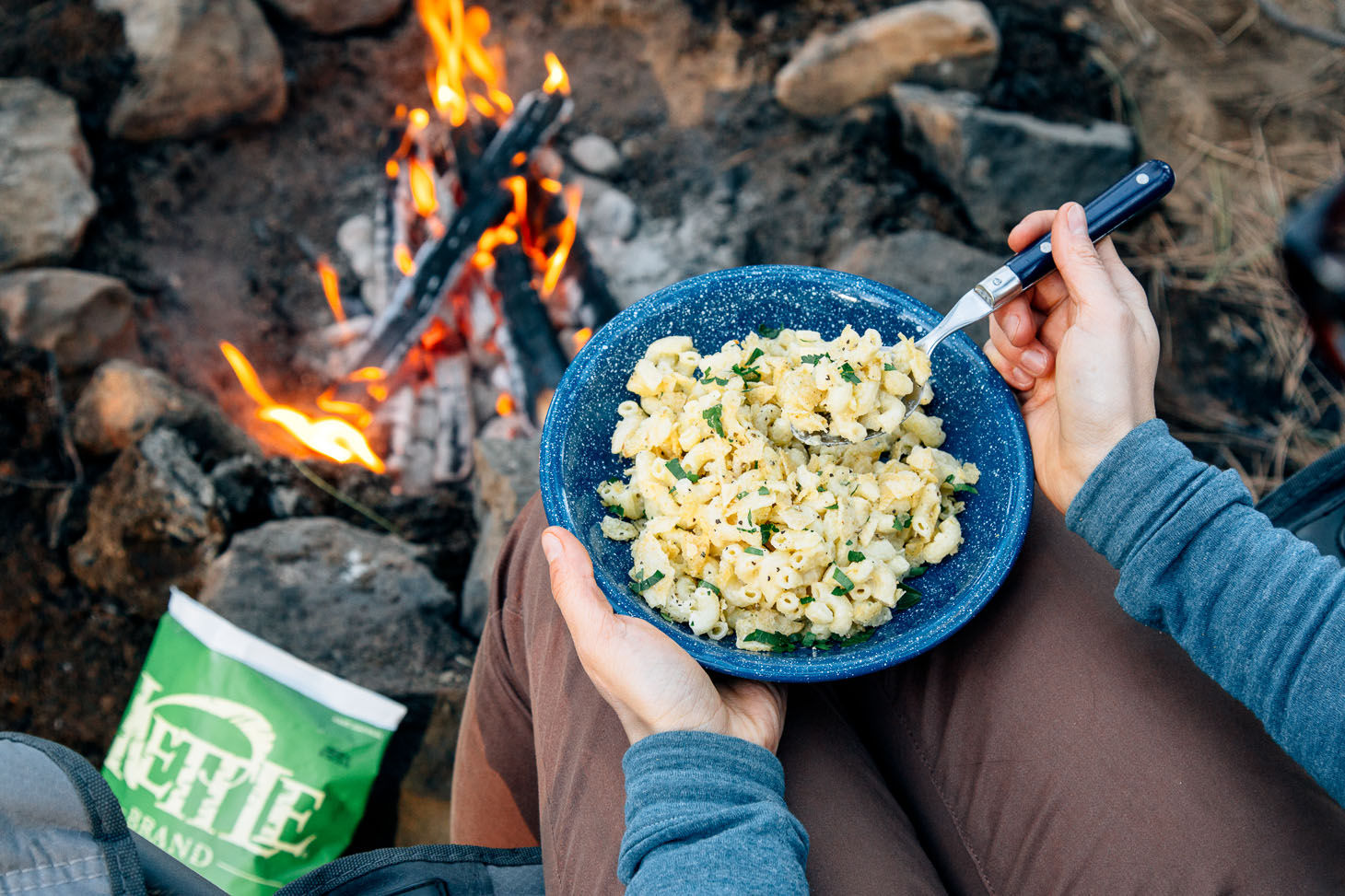 Mac and cheese in a blue camping bowl next to a fire.
