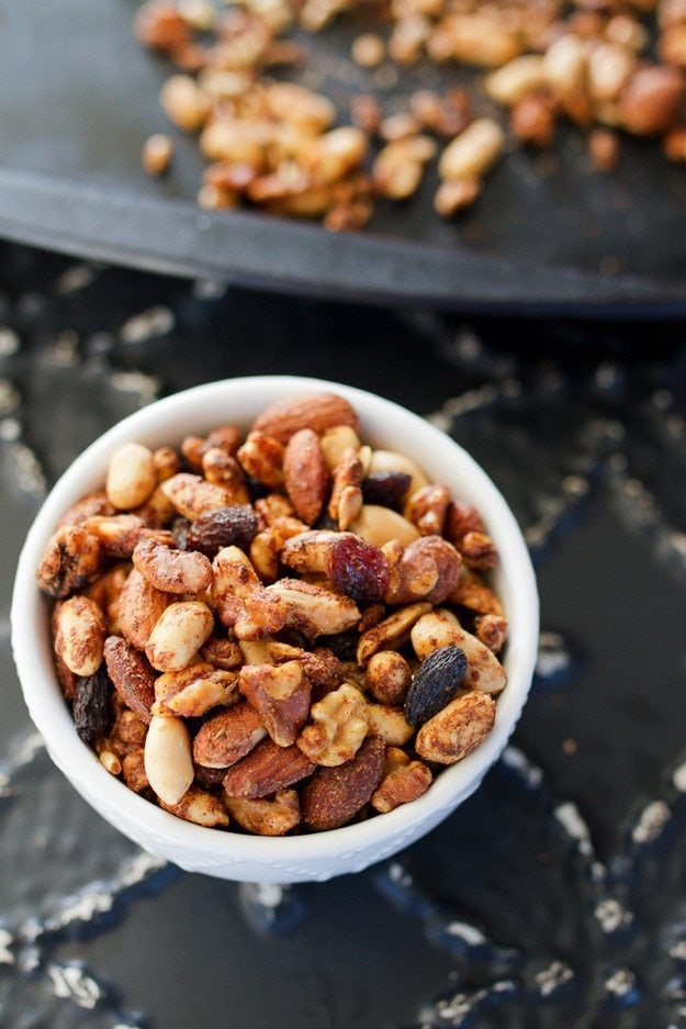 Trail mix in a white bowl on a dark surface