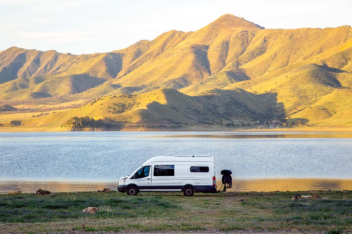 A white camper van parked in front of a lake with a grassy hill in the background