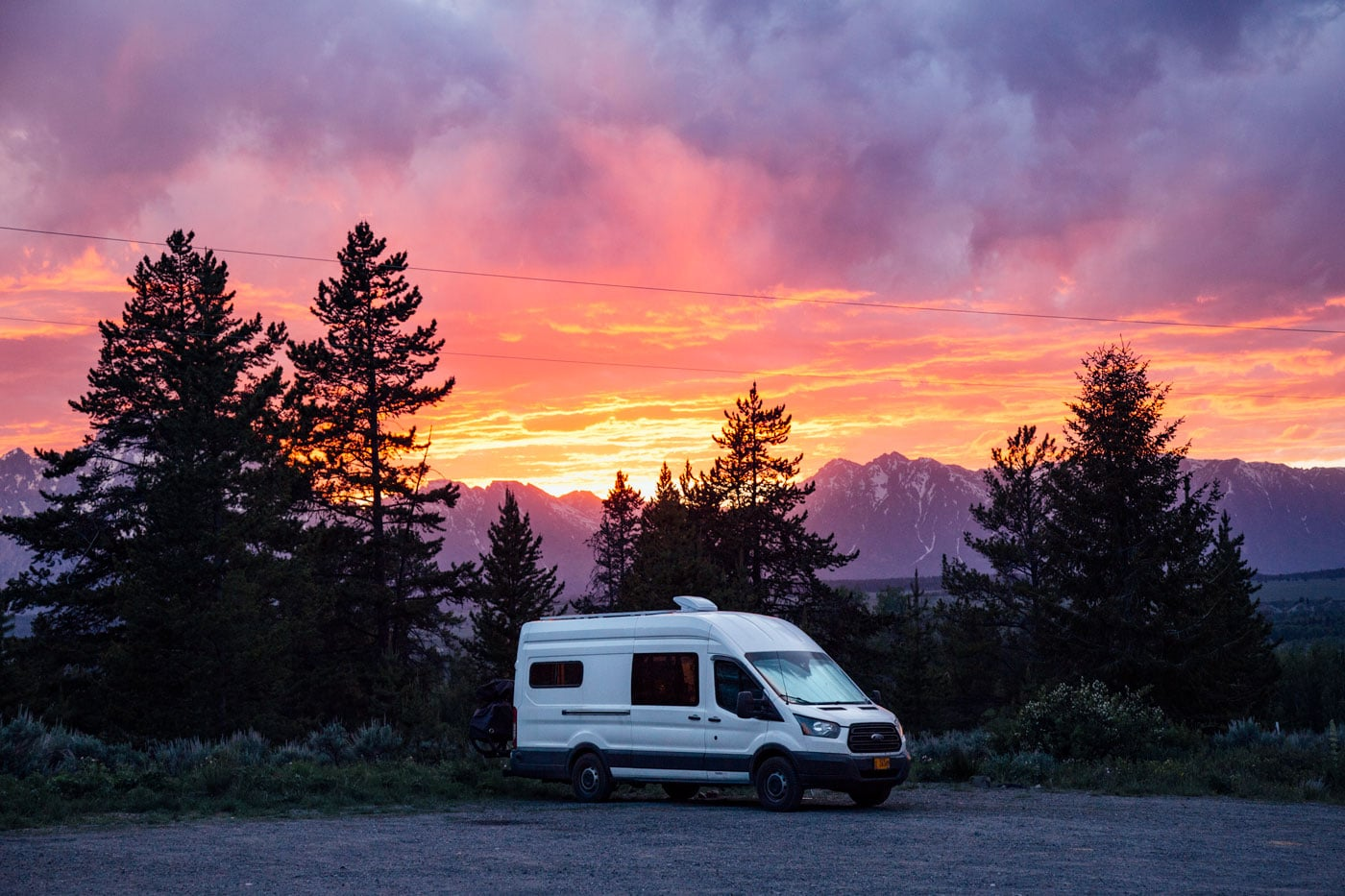 A campervan parked with a sunset and the Teton mountains in the background