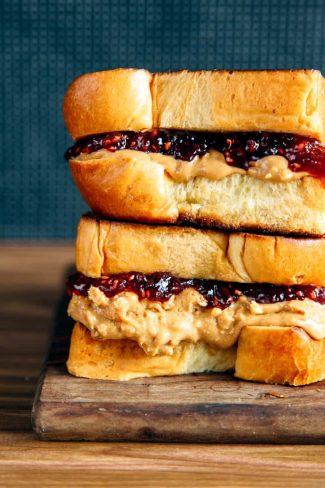 Brioche pb&j sandwich stacked on a wooden board