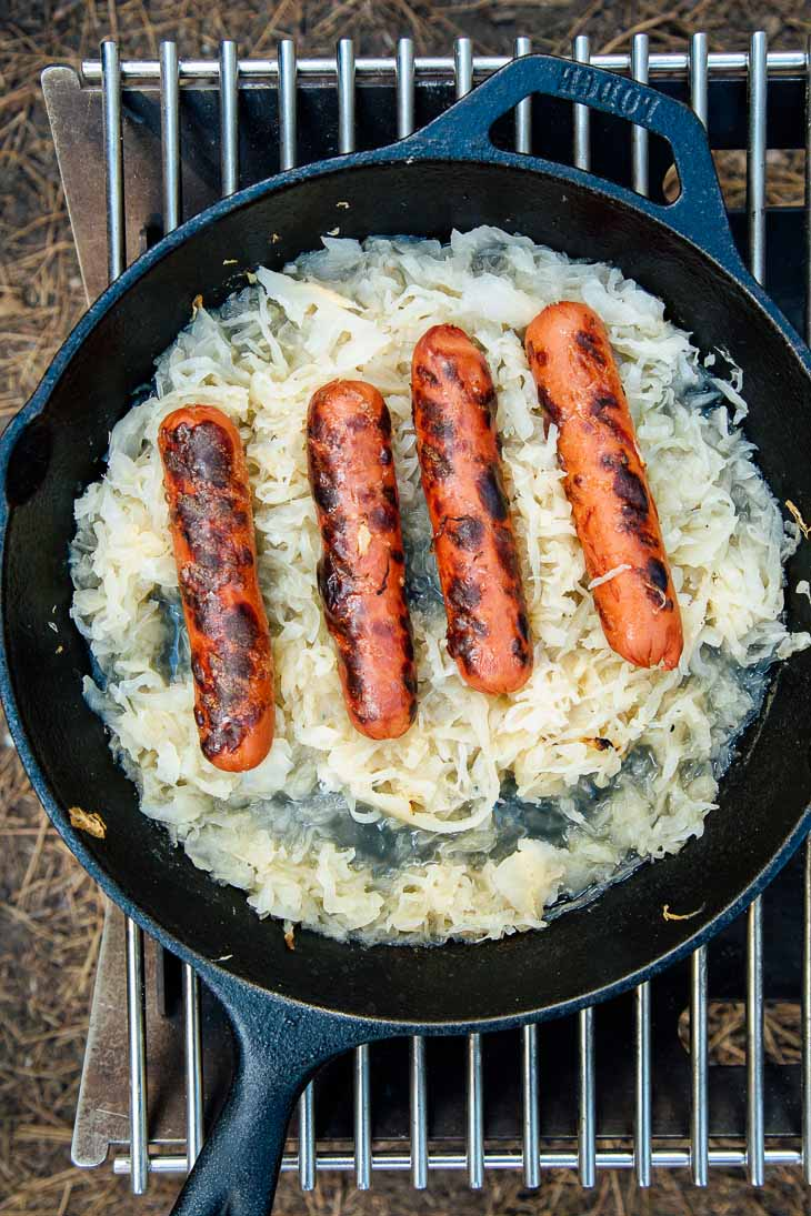 A skillet of sauerkraut and grilled hot dogs