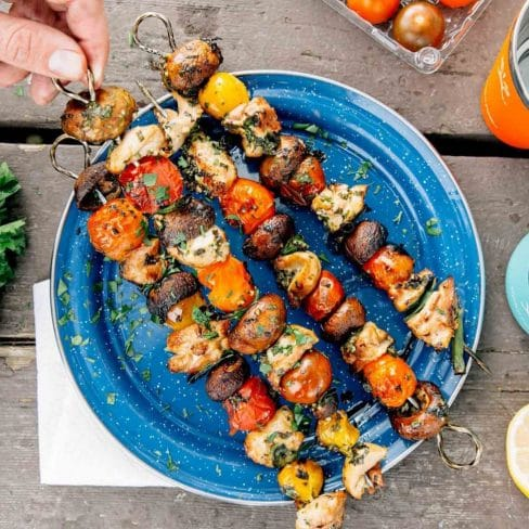 Four kabobs with chicken and vegetables on a blue plate. A hand is reaching in to pick one up.