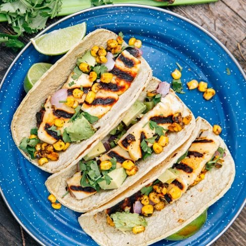 Three tacos filled with grilled halloumi cheese, corn, and avocado on a blue plate