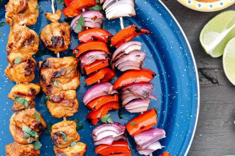 Two grilled chicken skewers next to two grilled pepper and onion skewers on a blue plate.
