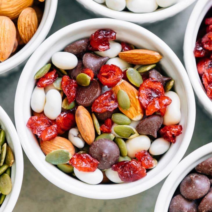 Almonds, pepitas, yogurt raisins, chocolate chips, and dried cranberries in a white dish