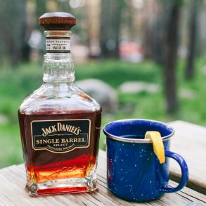 A blue mug next to a bottle of whiskey