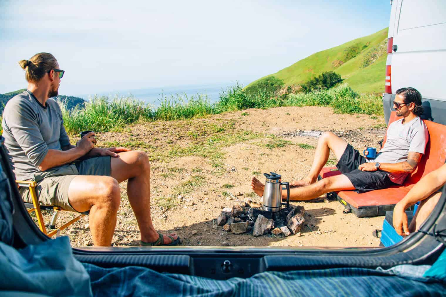 Two men sitting around a campfire in Big Sur