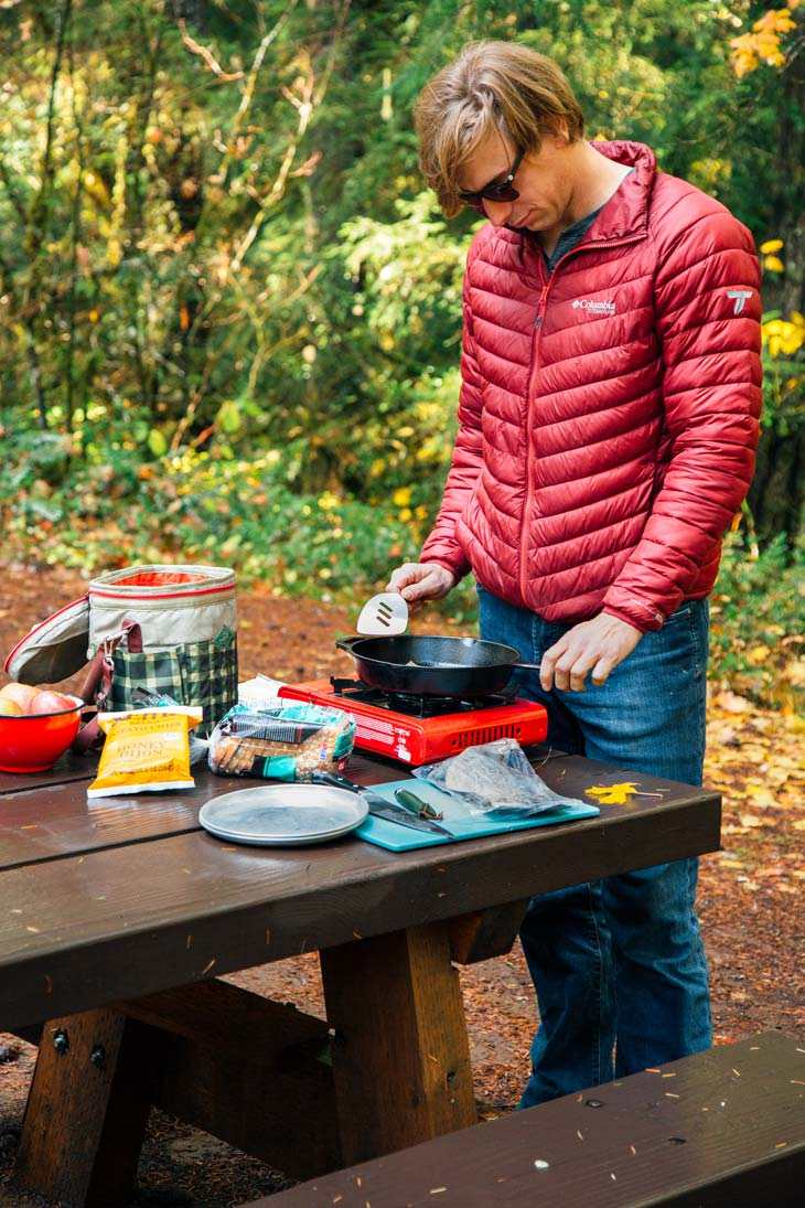 Michael standing at a camping table cooking over a camp stove