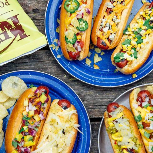 Three blue plates with hotdogs in buns and various toppings