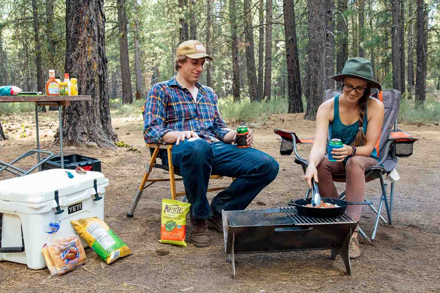 A camp scene with Megan and Michael cooking on a grill