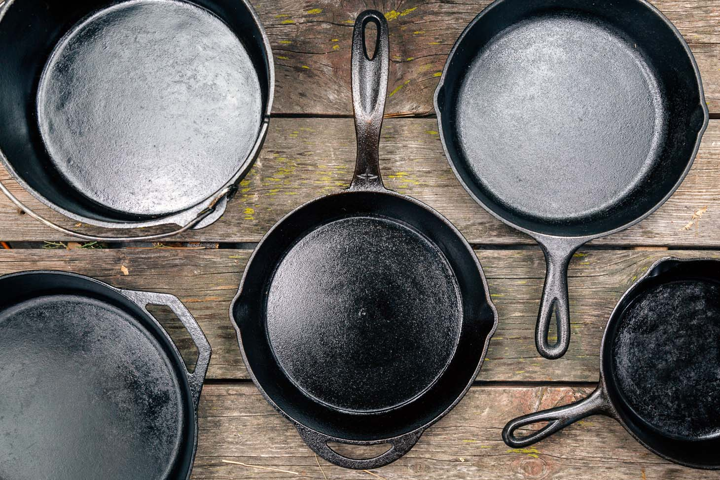 Cast iron skillets and Dutch oven on a wooden surface