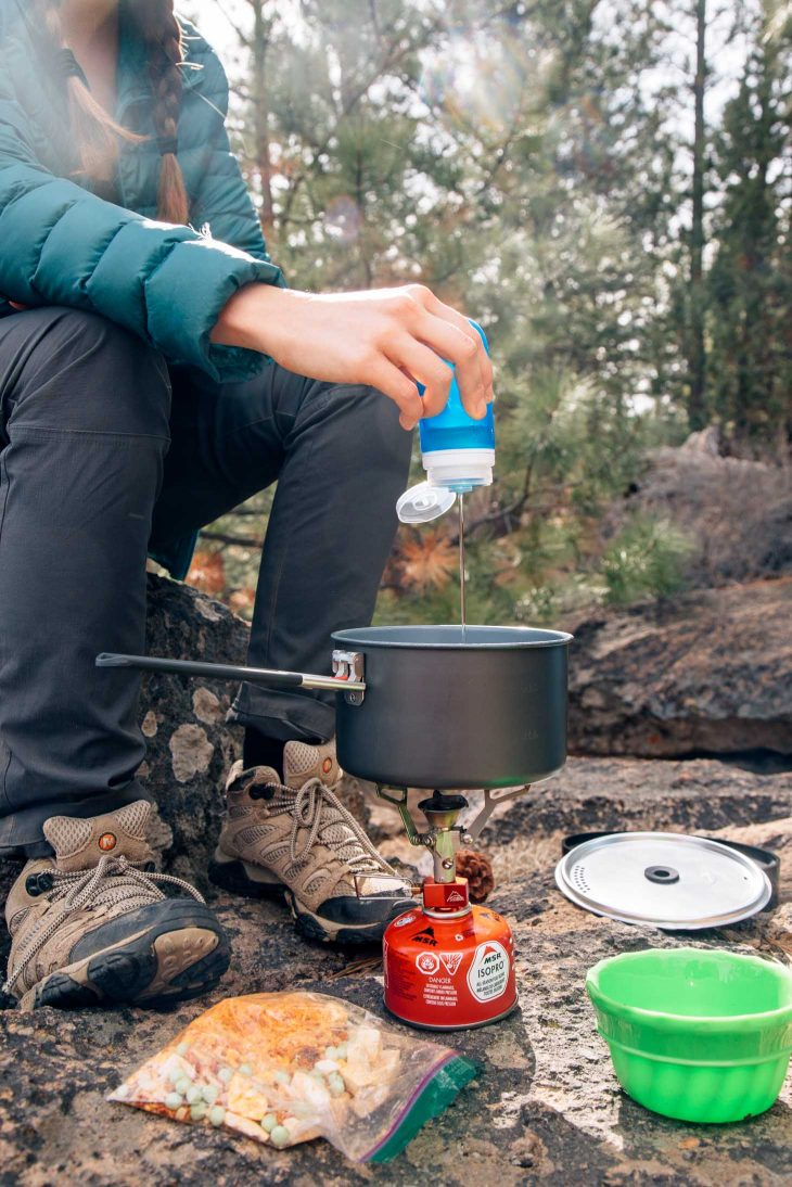 Pouring oil from a blue humangear gotoob+ into a backpacking meal