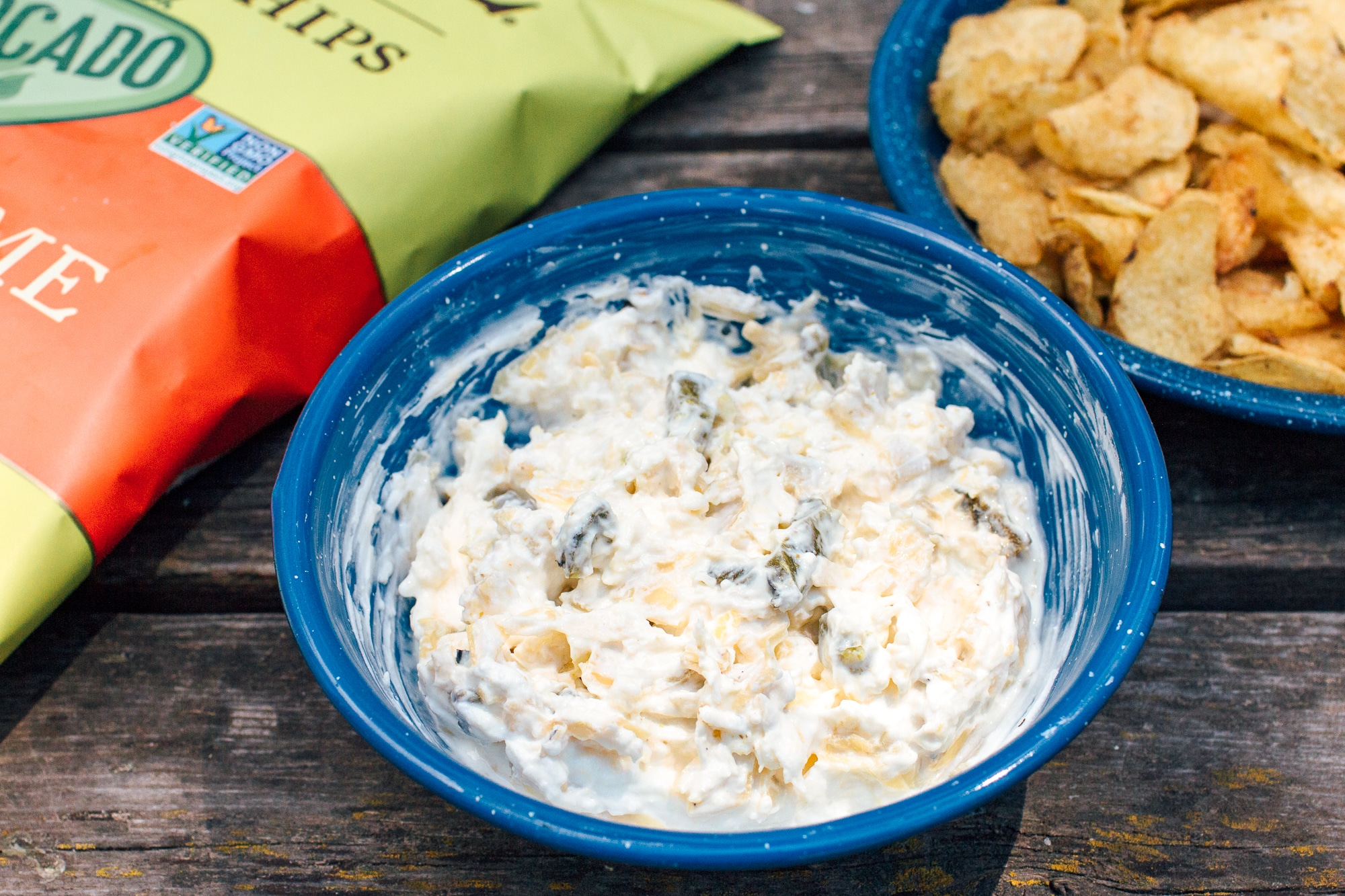 Jalapeno Artichoke dip in a blue enamel bowl on a wooden surface.