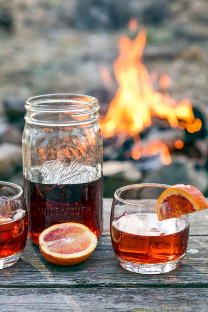 Negroni cocktail in a mason jar on a table in front of a campfire.