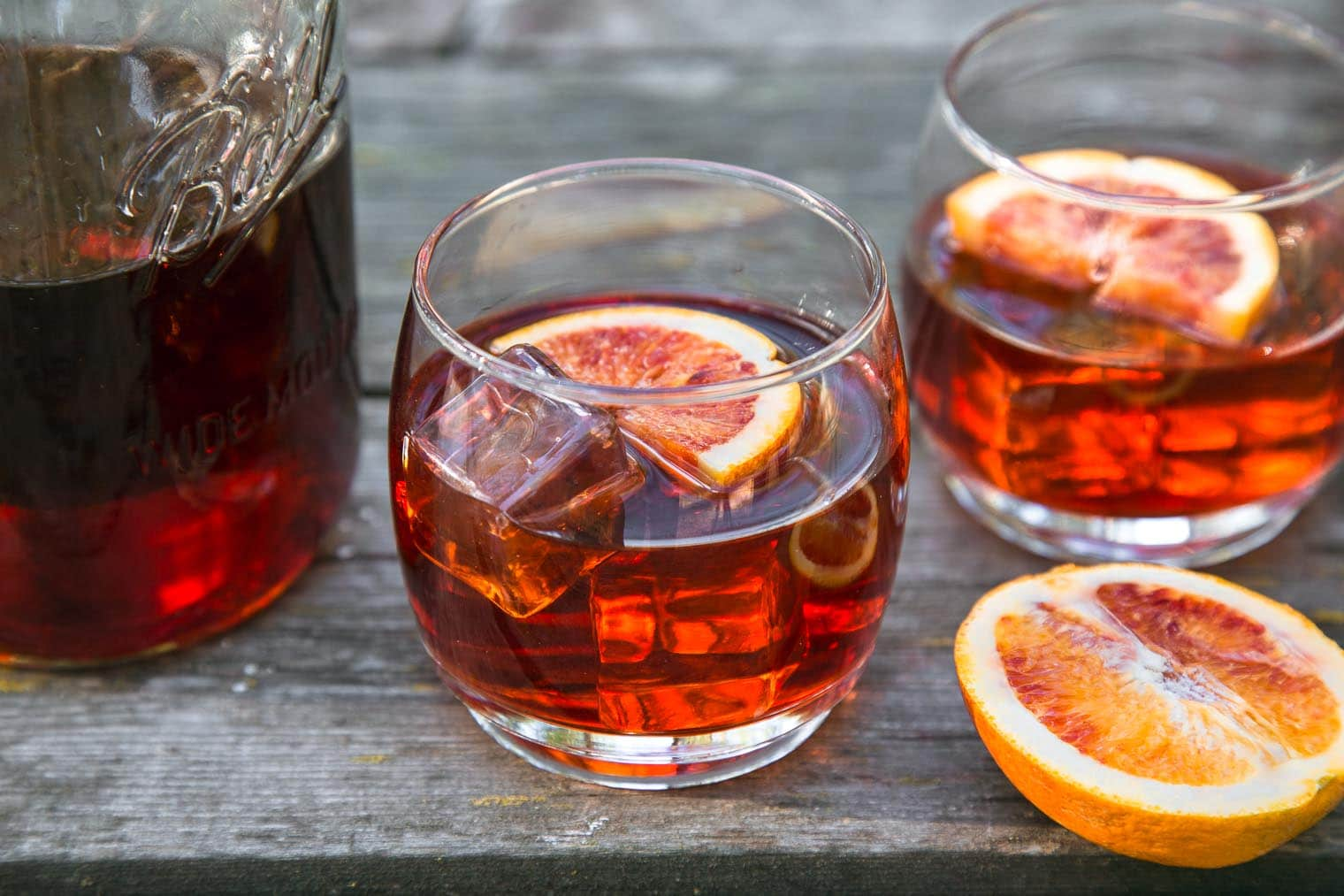 Negroni cocktail in a rocks glass on a wooden camping table.