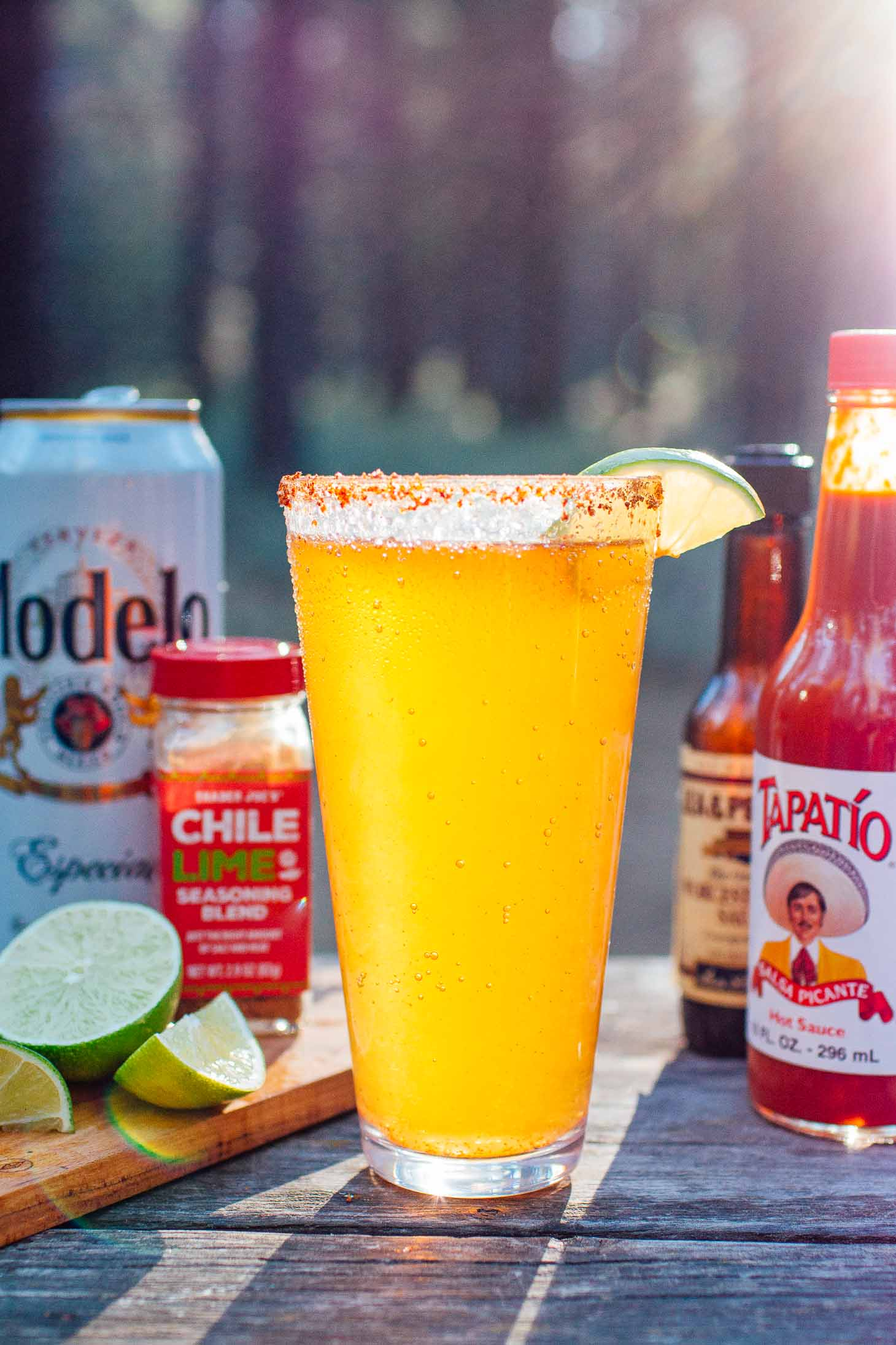 Michelada and ingredients with a forest background