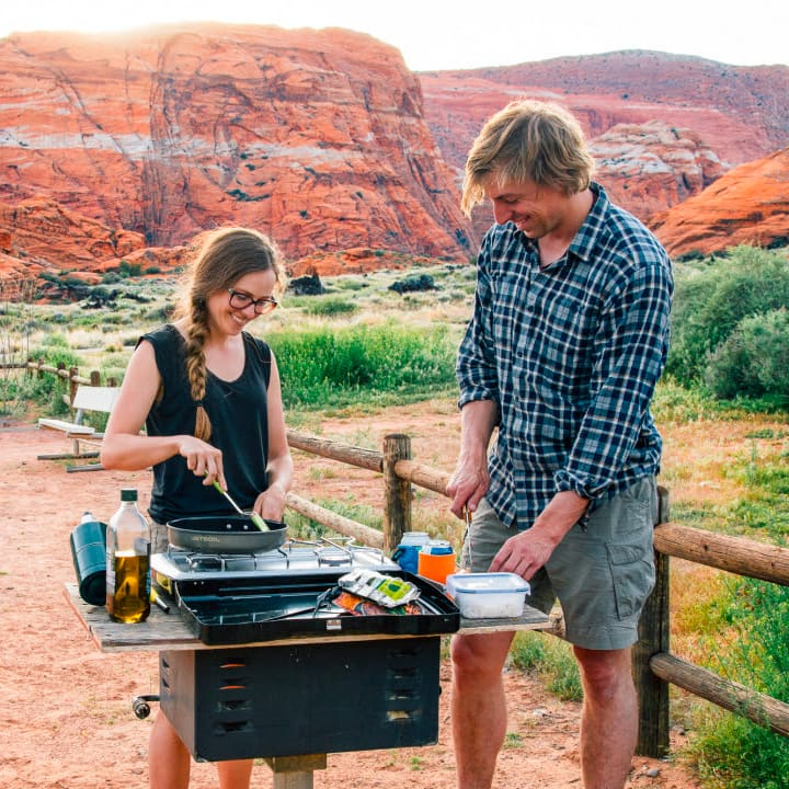 Megan and Michael cooking at a camp site next to each other with red rocks in the background