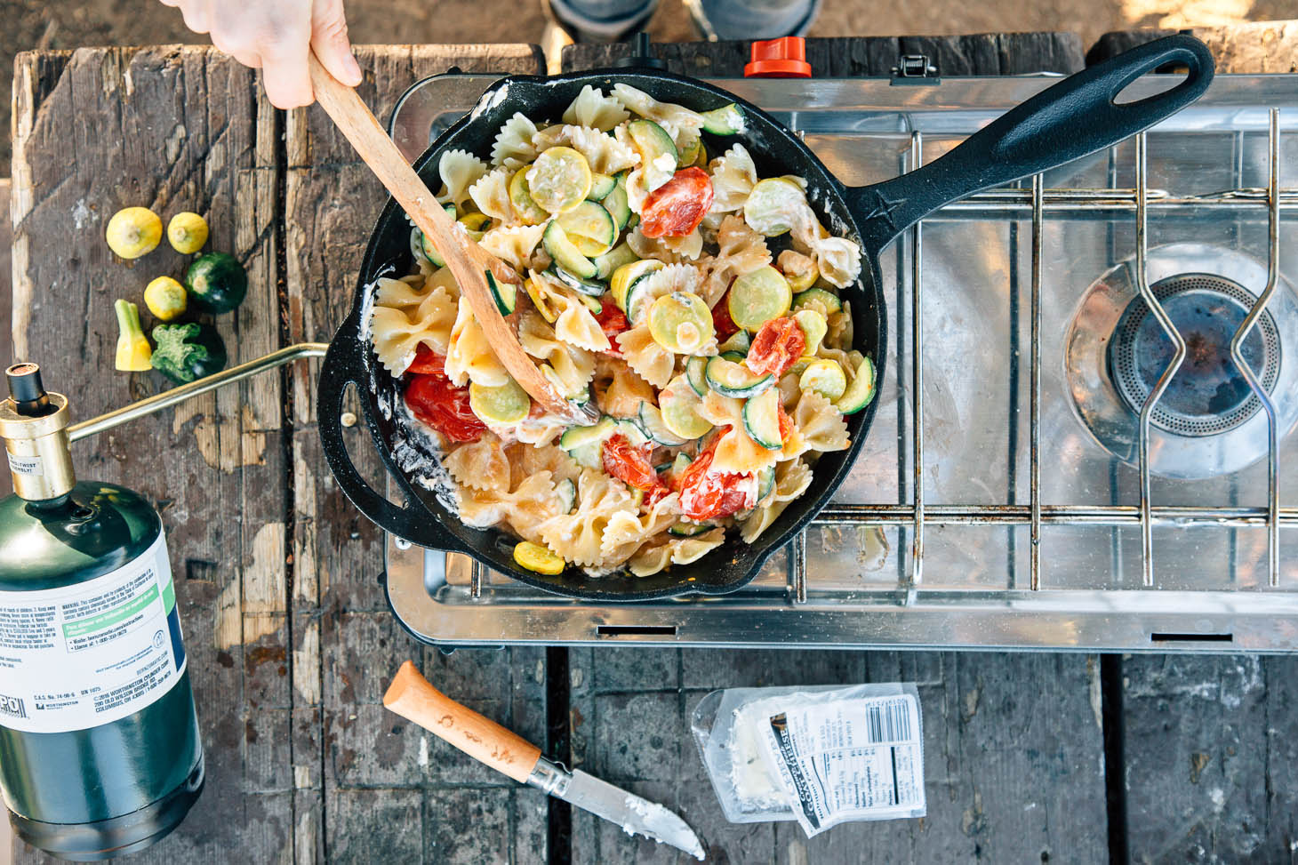 Squash, zucchini, tomatoes, and pasta in a cast iron skillet on a camping stove.