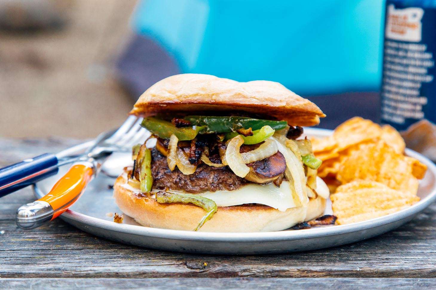 A burger topped with green peppers and onions on a blue plate and camping scene in the background