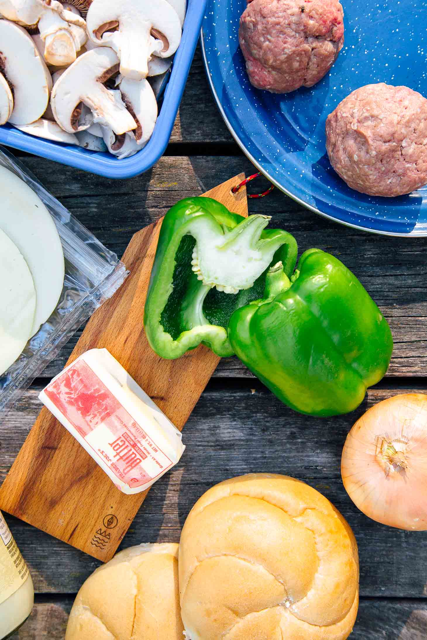 Ingredients on a table including green bell peppers, onion, buns and burger meat.