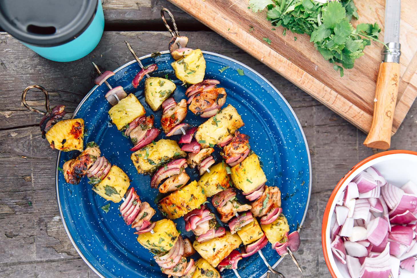 Pineapple chicken kabobs on a blue camping plate