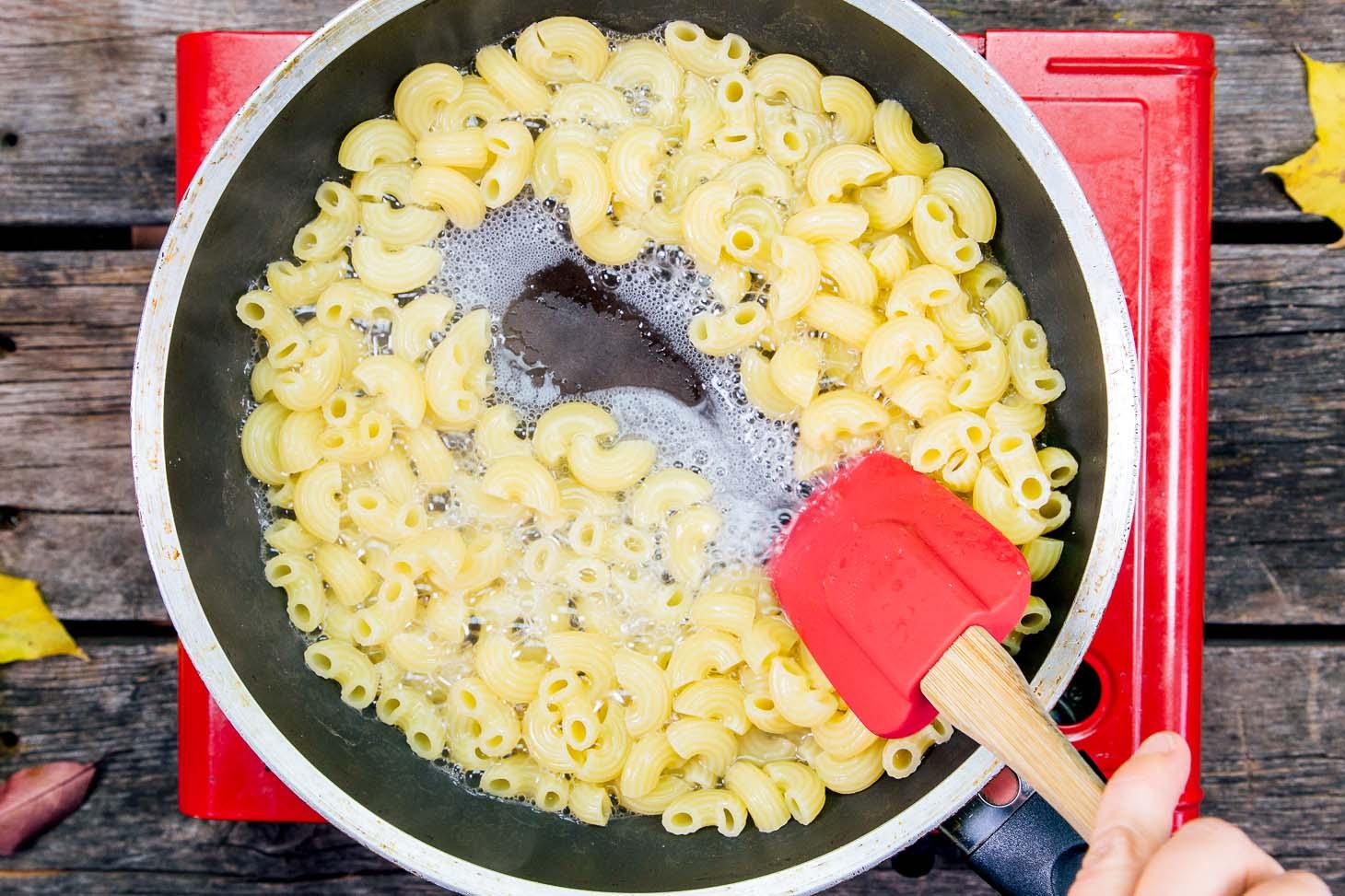 Stirring noodles in a skillet