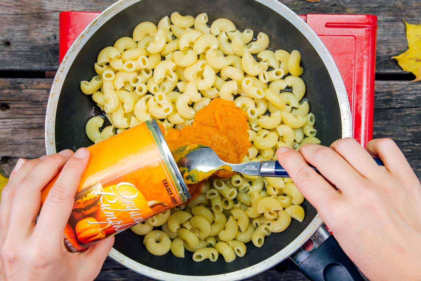 Scooping pumpkin puree into a skillet of noodles